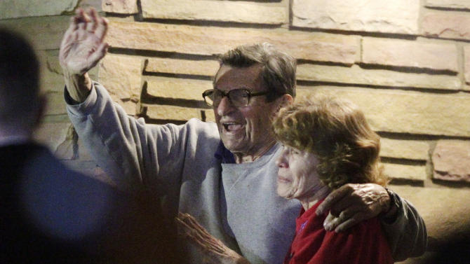 FILE - In this Nov. 9, 2011 file photo, former Penn State Coach Joe Paterno and his wife, Sue Paterno, stand on their porch to thank supporters gathered outside their home in State College, Pa.  A new era is dawning at Penn State, with a new football coach and a new look to the uniforms. But no Paterno on the sideline in a season opener for the first time since 1965. Penn State plays Ohio on Saturday. (AP Photo/Gene J. Puskar, File)