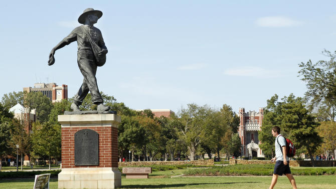 A student walks past the Seed Sower statue on the south oval at the University of Oklahoma in Norman, Okla., Monday, Sept. 12, 2011. A person with knowledge of the situation says Texas and Oklahoma officials met over the weekend amid speculation that the Sooners are considering leaving the Big 12. (AP Photo/Sue Ogrocki)