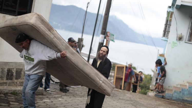 A man from a Jewish community receives help from a villager while carrying a mattress as he and fellow members prepare to leave the village of San Juan La Laguna
