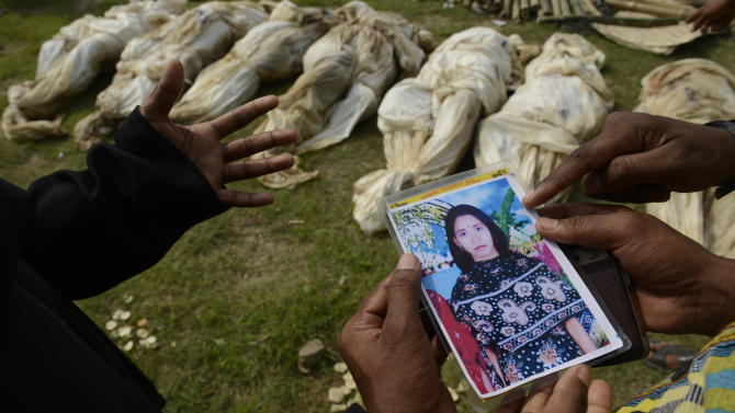 In this photograph taken on Wednesday, May 1, 2013, in Dhaka, Bangladesh, Farida, left, shows a picture of her sister-in-law Fahima to officials as she tries to identify her among the bodies which arrived for burial.  Just moments before Fahima was to be placed in one of the dozens of unmarked graves dug for victims of Bangladesh's building collapse, Farida was able to claim and leave with her sister-in-law's body. For Farida and countless other relatives of the garment workers who disappeared when Rana Plaza came crashing down, the past week has been one of tumbling expectations, as hope that their loved ones survived faded into the realization that they may have to return home without even a body to bury. (AP Photo/Ismail Ferdous)