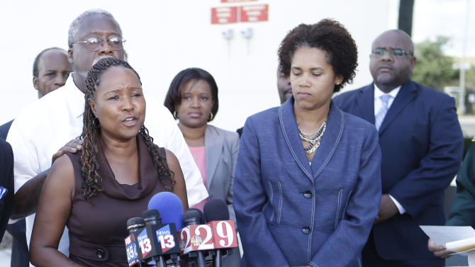 Lillie Danzy, front left, mother of escaped inmate Charles Walker,pictured in lower right, with her husband Jeff Danzy, to her left, and attorney Rhonda Henderson, right, listen as she makes a plea for her son to turn himself in to authorities during a news conference at the Orange County Sheriff's Office in Orlando, Fla., Saturday, Oct. 19, 2013. Joseph Jenkins and Walker, two convicted killers freed by bogus paperwork, are at large.(AP Photo/John Raoux)