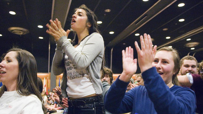 FILE - In this Friday, Feb. 17, 2012 file photo, Mackenzie DeRoyter of Spokane, Wash., center, and Hanna McCoy of Hawaii cheer for Republican presidential candidate Ron Paul while he speaks at the Student Union Building in Moscow, Idaho. Something's going on in America this election year: a renaissance of an ideal as old as the nation itself - that live-and-let-live, get-out-of-my-business, individualism vs. paternalism dogma that is the hallmark of libertarianism. But what looms are far larger questions about whether an America fed up with government bans and government bailouts - with government, period - is seeing a return to its libertarian roots. (AP Photo/Moscow-Pullman Daily News, Geoff Crimmins)