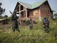Rebels of the M23 group stand near a deserted house after their troops entered the town of Rutshuru that had already been deserted by the Congolese army, near the Ugandan border. Rebel fighters in the Democratic Republic of Congo seized control Sunday of more towns in the country's east, but said they would cede most of their gains to UN peacekeepers and police