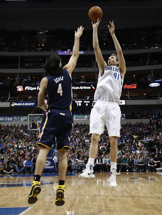 Dallas Mavericks power forward Dirk Nowitzki (41), of Germany, shoots the ball over Indiana Pacers' Luis Scola (4), of Argentina, during the first half of an NBA game, Sunday, Mar. 9, 2014, in Dal