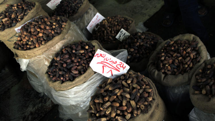 """Various brands of dates are on display for sale, a main item in the  Egyptians' food supplies list of the holy month of Ramadan that starts August first this year, in Cairo, Egypt Sunday, July 31, 2011. Arabic reads """"Tahrir Square dates"""" which is an expensive dates brand named after the famous square that witnessed most of the Egyptian revolution's events. (AP Photo/Nasser Nasser)"""