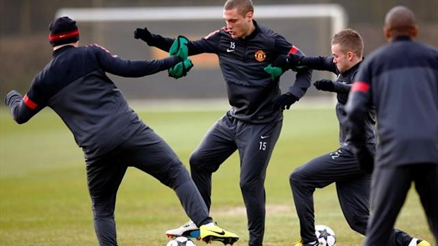 Manchester United's Tom Cleverley and Wayne Rooney challenge Nemanja Vidic during a training session at Carrington (Reuters)