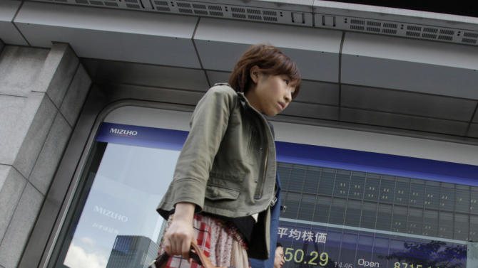 People walk past an electronic stock indicator in Tokyo Wednesday, May 23, 2012. Japan's Nikkei 225 index fell 1.98 percent to 8,556.60 as a report that Greece is considering preparations to leave the euro common currency sent Asian stock markets lower Wednesday. (AP Photo/Shizuo Kambayashi)