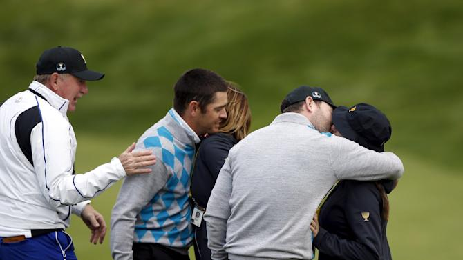 International team member Oosthuizen and Grace celebrate with Nel-Mare, Oosthuizen's wife and Coetzee, Grace's girlfriend, after defeating U.S. team members Reed and Fowler during the foursome matches of the Presidents Cup golf tournament in Incheon