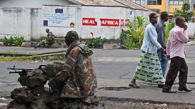 People walk past as M23 rebel soldier's take positions near the Heal Africa hospital in the center of  Goma, Congo, Tuesday, Nov. 20, 2012. A rebel group created just seven months ago seized the strategic provincial capital of Goma, home to more than 1 million people in eastern Congo, and its international airport on Tuesday, officials and witnesses said, raising the specter of a regional war. (AP Photo/Melanie Gouby)