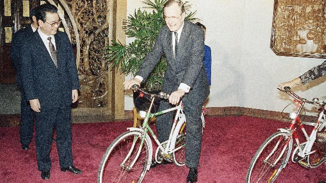 """FILE - In this Saturday, Feb. 25, 1989, file photo, China's Premier Li Pang, left, watches U.S. President George H.W. Bush, try out one of two new """"Flying Pigeon"""" bikes presented by Pang, left, for the President and the First Lady in Beijing. (AP Photo/Doug Mills, File)"""