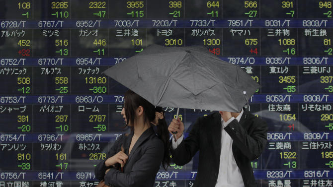 A couple shares an umbrella as they take shelter from the rain in front of the electronic stock board of a securities firm in Tokyo Friday, June 1, 2012. Asian stock markets fell Friday, stunted by weakness in Chinese manufacturing that suggests the slowdown in the world's No. 2 economy may worsen. Japan's Nikkei 225 index dropped 102.48 points to close at 8440.25 yen. (AP Photo/Itsuo Inouye)