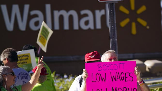 Demonstrators protest Wal-Mart in Boynton Beach, Fla., Friday, Nov 23, 2012. Wal-Mart employees and union supporters are taking part in today's nationwide demonstration for better pay and benefits A union-backed group called OUR Walmart, which includes former and current workers, was staging the demonstrations and walkouts at hundreds of stores on Black Friday, the day when retailers traditionally turn a profit for the year. (AP Photo/J Pat Carter)