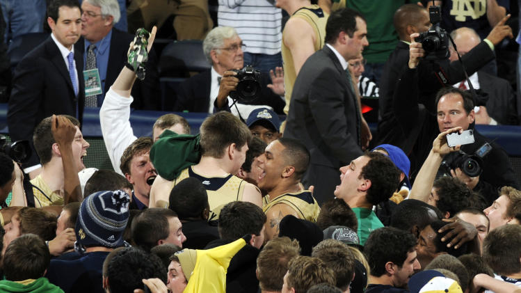 Notre Dame players including Zach Auguste, center right, and Jack Cooley, center left, celebrate with fans after their 104-101 win over Louisville in the fifth overtime of their NCAA college basketball game, Saturday, Feb. 9, 2013, in South Bend, Ind. (AP Photo/Joe Raymond)