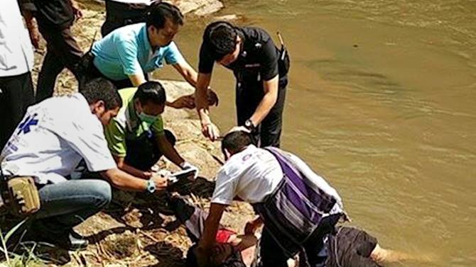 Thai policemen attend to the body of a mahout killed by his elephant in Chiang Mai province on August 26, 2015