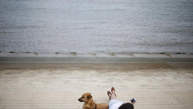 A woman rests next to her dog near Tagus river in Lisbon