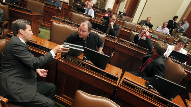 Rep. Keith Downey, left, talks to Rep. Branden Petersen on the house floor on Thursday night June 30, 2011 as they await the government shutdown in the capitol in St. Paul, Minn.  The Minnesota state government shutdown at 12:01 a.m. CDT Friday July 1,2011.   (AP Photo/Carlos Gonzalez/STAR TRIBUNE) -- MAGS OUT, MINNEAPOLIS AREA TV OUT, MANDATORY CREDIT --