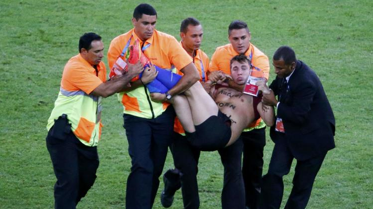 Stewards carry a supporter off the pitch during the 2014 World Cup final between Germany and Argentina at the Maracana stadium in Rio de Janeiro
