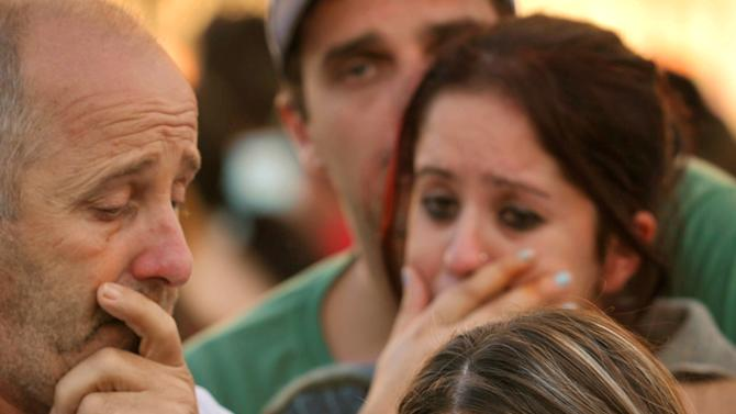ALTERNATIVE CROP OF XSI107.- Relatives of victims react as they wait for news near the Kiss nightclub in Santa Maria city,  Rio Grande do Sul state, Brazil, Sunday, Jan. 27, 2013.  According to police more than 200 died in the devastating nightclub fire in southern Brazil.  Officials say the fire broke out at the club while a band was performing. (AP Photo/Ronald Mendes-Agencia RBS)