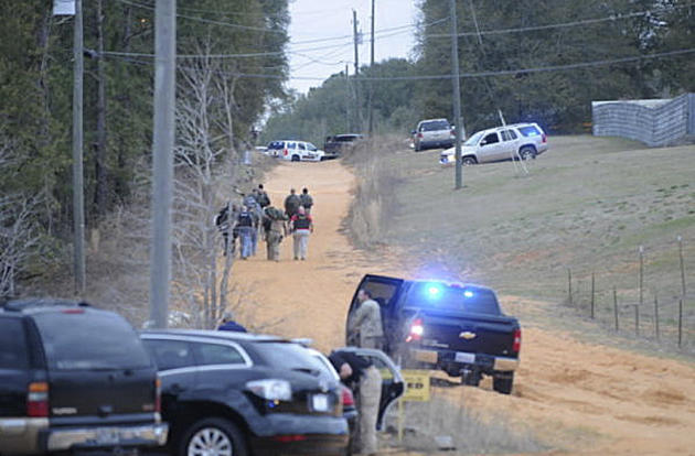 In this Tuesday, Jan 29, 2013 photo, law enforcement officers walk up the road toward a home where a school bus shooting suspect was hiding inside a bunker late Tuesday. Police, SWAT teams and negotia