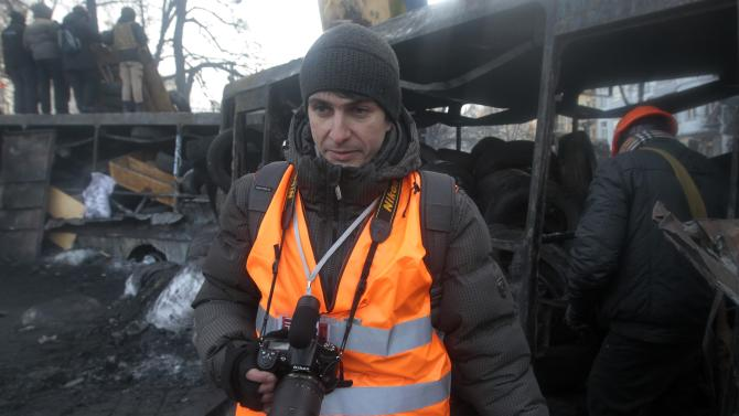 In this photo taken Monday, Jan. 27, 2014, journalist Ihor Medelyan, 32, talks to the Associated Press in an interview near barricades in central Kiev, the site of violent clashes between protesters and police. Medelyan quit the government-owned First National channel after the government violently dispersed a small peaceful protest rally and after his channel refused to objectively report on the event. (AP Photo/Sergei Chuzavkov)