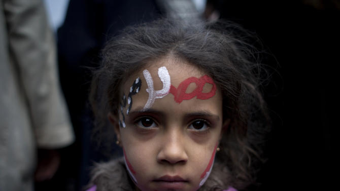 "A girl with the colors of Egypt's national flag and Arabic that reads, ""Egypt, Morsi,"" painted on her face attends a demonstration in front of Egypt's top court, in Cairo, Egypt, Sunday, Dec. 2, 2012. Egypt's top court announced on Sunday the suspension of its work indefinitely to protest ""psychological and physical pressures,"" saying its judges could not enter its Nile-side building because of the Islamist president's supporters gathered outside. (AP Photo/Nasser Nasser)"