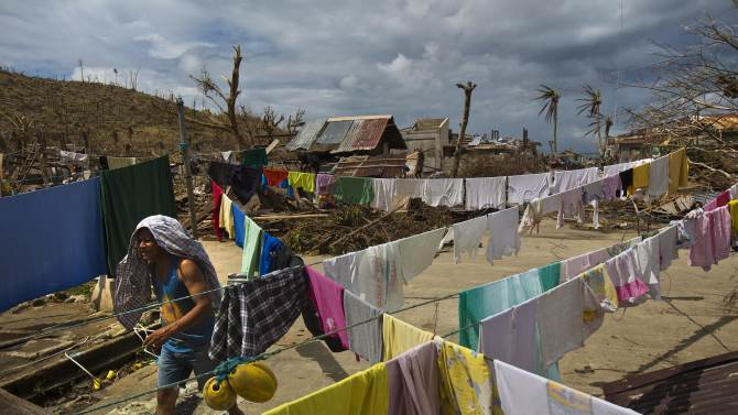 In this Thursday, Nov. 14, 2013 photo, Typhoon Haiyan survivor walks past drying laundry in the ruins in the village of Marabut, Philippines. The Philippines has received an outpouring of international aid running into hundreds of millions of dollars but much of it has been stuck in a bottleneck outside the affected areas. (AP Photo/David Guttenfelder)