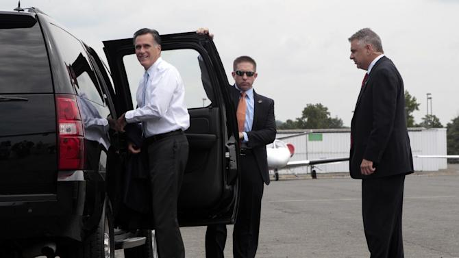 Secret Service agents stand guard as Republican presidential candidate, former Massachusetts Gov. Mitt Romney gets into his vehicle upon his arrival in Charlotte, N.C., Wednesday, Aug. 15, 2012. (AP Photo/Mary Altaffer)