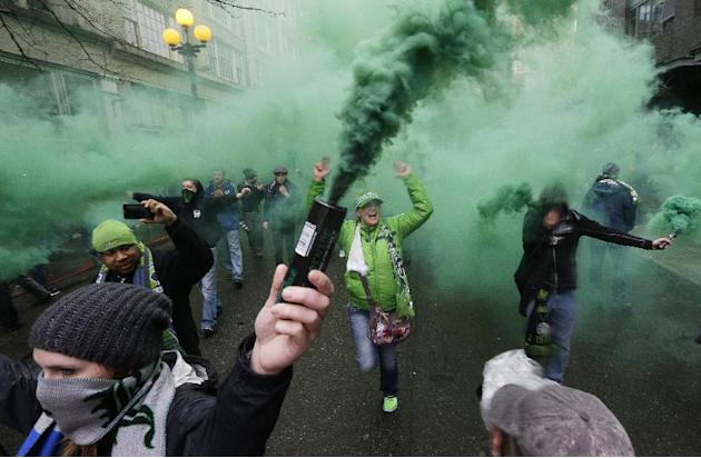 "Members of the Emerald City Supporters and other fan groups burn smoke devices as they take part in the traditional ""March to the Match"" before the Seattle Sounders season-opening MLS soccer"