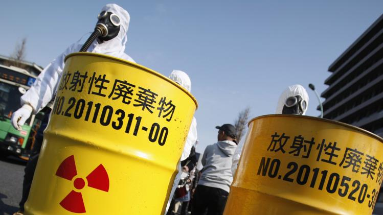 Anti-nuclear protesters wearing protective suits push mock drums which are labelled as radioactive waste from Kansai Electric Power Co's Ohi nuclear power plant and TEPCO's Fukushima nuclear power plant, as they march in Tokyo