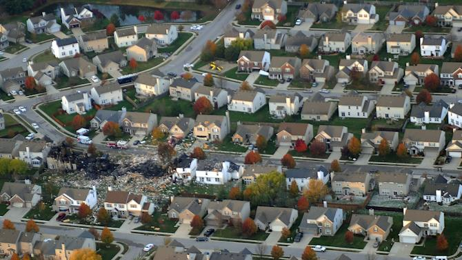 This aerial photo shows the two homes that were leveled and the numerous neighboring homes that were damaged from a massive explosion that sparked a huge fire and killed two people, Sunday, Nov. 11, 2012, in Indianapolis.  Nearly three dozen homes were damaged or destroyed, and seven people were taken to a hospital with injuries, authorities said Sunday. The powerful nighttime blast shattered windows, crumpled walls and could be felt at least three miles away. (AP Photo/The Indianapolis Star, Matt Kryger)  NO SALES