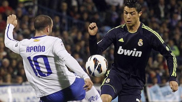 Real Madrid's Cristiano Ronaldo (R) challenges Zaragoza's Apono during their Spanish First division match