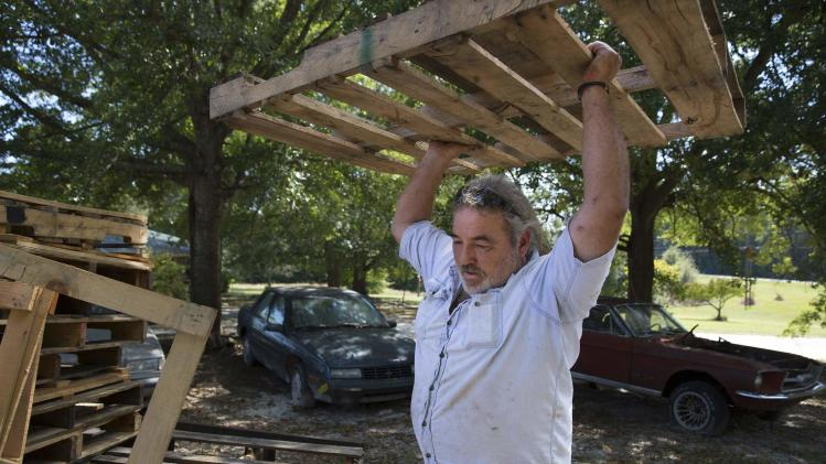 Richard Smith, who was laid off from a factory owned by BWAY in 2010, moves wooden pallets in his front yard in Toccoa