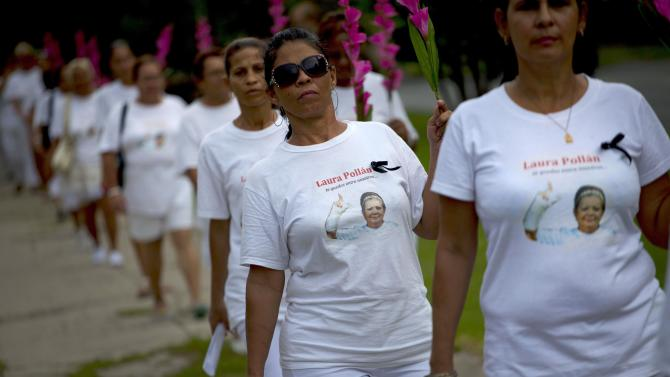 "Members of Cuba's Ladies in White dissident group, wearing T-shirts with images of late co-founder of the group, Laura Pollan, participate in a march marking one year since the death of Pollan in Havana, Cuba, Sunday, Oct 14, 2012. The Ladies in White was formed in 2003 mostly by wives and family members of 75 dissidents jailed in a crackdown on dissent. Pollan had been married to one of the dissident prisoners, Hector Maseda. The T-shirts read in Spanish ""you stay with us."" (AP Photo/Ramon Espinosa)"