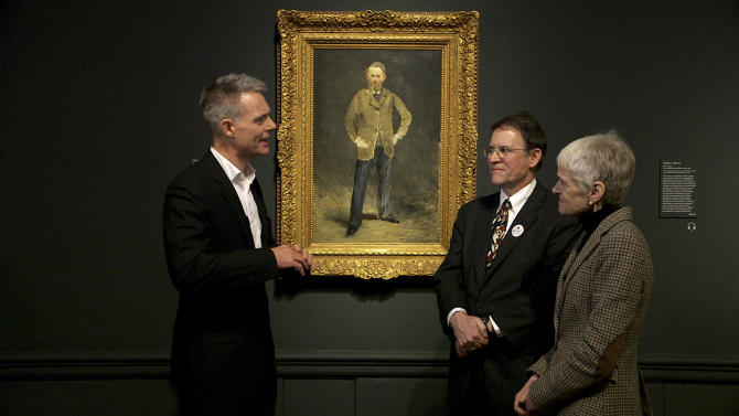 In this Jan. 2013 photo provided by Phil Grabsky Films, art historian Tim Marlow, left, curator Larry Nichols and the curator of the Manet exhibit at the Royal Academy of Arts Mary Anne Stevens talk in front of a Manet painting at the Royal Academy of Arts in London. On April 11, BY Experience is launching EXHIBITION, broadcasts of current or just closed art exhibitions from around the world to select movie theaters and performing arts centers in nearly 30 countries. (AP Photo/Phil Grabsky Films)