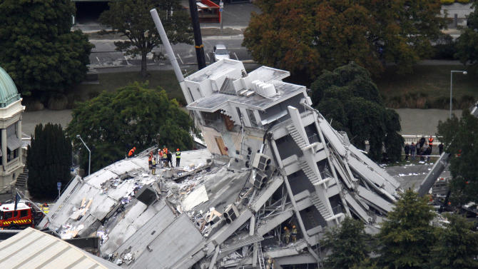 Rescue workers climb onto the collapsed Pyne Gould Guinness Building in central Christchurch, New Zealand, Tuesday, Feb. 22 2011. A powerful earthquake collapsed buildings at the height of a busy workday killing at least 65 people and trapping dozens in one of the country's worst natural disasters. (AP Photo/New Zealand Herald, Mark Mitchell) NEW ZEALAND OUT, AUSTRALIA OUT