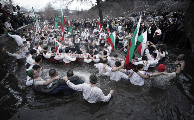 Believers sing and dance in the icy waters of river Tundzha as they celebrate Epiphany day in the town of Kalofer, Bulgaria, Sunday, Jan. 6, 2013. Traditionally, an Eastern Orthodox priest throws a cr