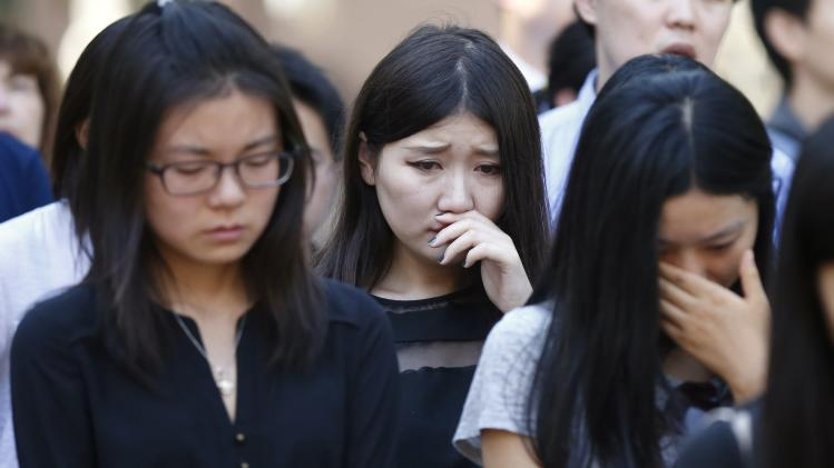 USC students and faculty watch a memorial service for murdered USC graduate student Ji Xinran on a television screen on the USC campus in Los Angeles