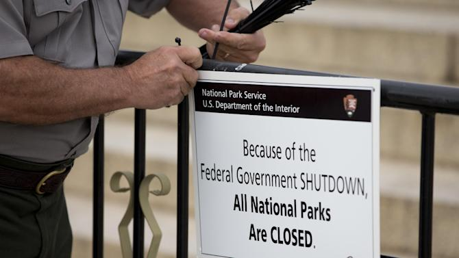 "A National Park Service employee posts a sign reading ""Because of the Federal Government SHUTDOWN All National Parks are Closed"" on a barricade closing access to the Lincoln Memorial in Washington, Tuesday, Oct. 1, 2013. Congress plunged the nation into a partial government shutdown Tuesday as a long-running dispute over President Barack Obama's health care law stalled a temporary funding bill, forcing about 800,000 federal workers off the job and suspending most non-essential federal programs and services. (AP Photo/Carolyn Kaster)"
