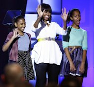 First lady Michelle Obama, center, and daughters Sasha, left, and Malia, right, react during the Kids&#39; Inaugural: Our Children. Our Future.&quot; event in Washington, Saturday, Jan. 19, 2013, as part of the 57th Inauguration weekend of events. (AP Photo/Frank Franklin II)