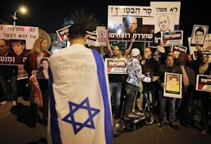 An Israeli demonstrator with an Israeli flag wrapped around himself takes part in a protest against the upcoming release of Palestinian prisoners, in Tel Aviv
