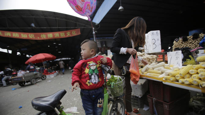 In this April 9, 2013 photo, a child waits for her mother who buys vegetable near the closed poultry section at the Huhuai agricultural market where the H7N9 bird flu was detected by authority in Shanghai, China. After a new and lethal strain of bird flu emerged in Shanghai two weeks ago, the government of China's bustling financial capital responded with live updates on a Twitter-like microblog. It's a starkly different approach than a decade ago, when Chinese officials silenced reporting as a deadly pneumonia later known as SARS killed dozens in the south. (AP Photo/Eugene Hoshiko)
