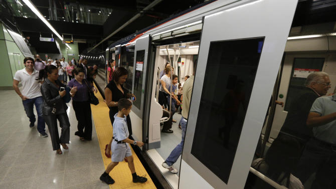 In this Wednesday, April 2, 2014 photo, government employees and their guests enter a subway while participating in an invitation to test the wagons of the new Panama Metro in Panama City. Central America's first underground metro will surely alleviate the booming capital's dreadful traffic. But critics say the $2 billion spent on the 14-kilometer rail project, which was marred by cost overruns, would've been better used building a higher-capacity, surface transport network. They also are blasting the timing of the over-the-top inauguration set for Saturday, April 5, which they say is a political stunt by President Ricardo Martinelli to drum up support for his preferred successor. (AP Photo/Arnulfo Franco)