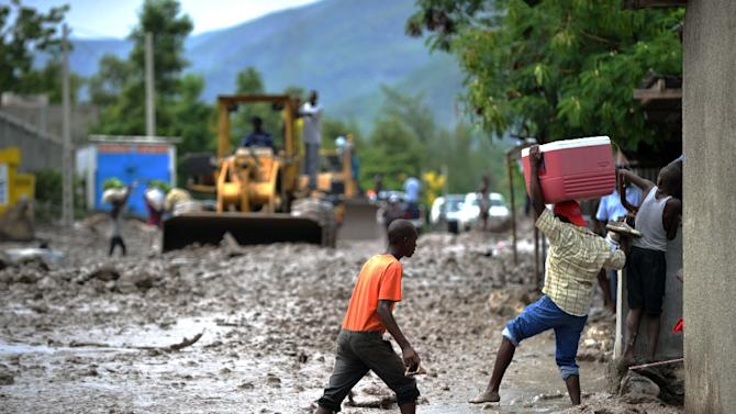 Haitians walk in the mud on Route Nationale 1 while a machine cleans the road after a mudslide caused by the rains from Tropical Storm Erika in Montrouis, Haiti, on August 29, 2015