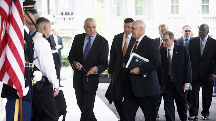 From left, Aetna CEO Mark Bertolini, Humana CEO Bruce Broussard, Blue Cross Blue Shield of Florida CEO Patrick Geraghty, and other health care chief executive officers arrive at the White House in Washington, Wednesday, Oct. 23, 2013, to meet with White House officials regarding President Barack Obama's health care law. (AP Photo/Charles Dharapak)