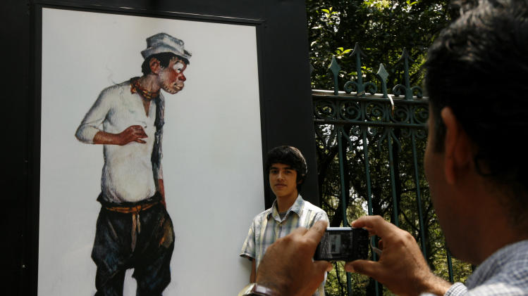 """In this Monday July 25, 2011 photo, a young man poses for a picture next to a photograph of the late Mexican comedian and actor Mario Moreno """"Cantinflas,"""" at an open-air exhibit in Mexico City. Mexico will celebrate the upcoming comedian's 100th birthday with a variety of events including; a book release and a commemorative stamp. Considered by some as the Charlie Chaplin of Mexico, Moreno starred in 51 films and shorts, winning a Golden Globe for best comedy actor for his role in """"Around the World in 80 Days."""" in 1957. (AP Photo/Marco Ugarte)"""