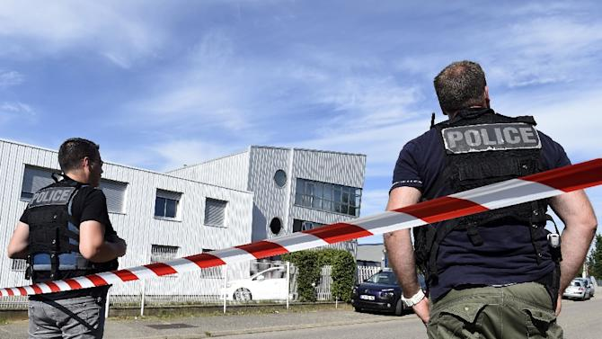 French police officers stand guard near a cordon outside the delivery service company in Chassieu on June 26, 2015, where the victim who was decapitated worked