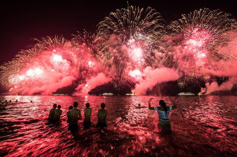People react to the fireworks celebrating the New Year on Copacabana beach in Rio de Janeiro, Brazil, on January 1, 2014