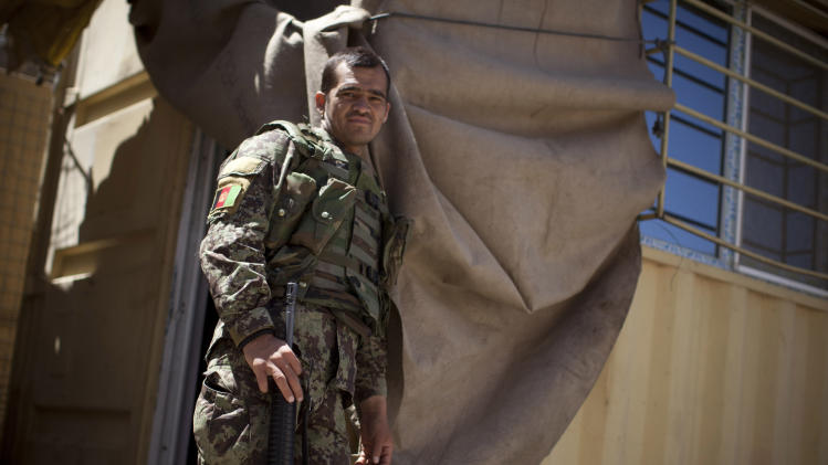 In this Tuesday, May 22, 2012 photo, an Afghan National Army soldier relaxes next to his sleeping quarter at Chinari outpost in Logar province, east Afghanistan. The months-old outpost was built after a police post at the base of the hill was attacked and destroyed by Taliban forces. (AP Photo/Anja Niedringhaus)