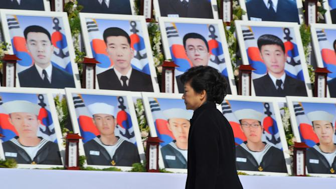 """South Korean President Park Geun-hye walks by the portraits of some of 46 South Korean sailors who were killed in the sinking of their war ship """"Cheonan,"""" at the National Cemetery in Daejeon, South Korea, Tuesday, March 26, 2013. An explosion ripped apart the 1,200-ton warship, killing 46 sailors near the maritime border with North Korea in 2010. The sailors are buried here in the city. South Korea marks three years from the incident on March 26. (AP Photo/Kim Jae-hwan, Pool)"""