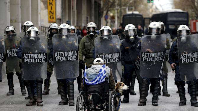 A handicapped protester and his dog face a riot police cordon outside the Agriculture ministry following clashes during a protest against planned pension reforms in Athens